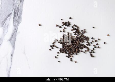 Cumulo di pepe nero in grani di pepe su marmo bianco sullo sfondo di texture. Vista superiore, spazio. Foto Stock