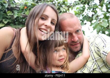 Bella famiglia felice cuddling selfie picture lunghi capelli scuri giovane con bambino Foto Stock