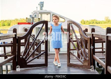 Fashion kid concetto di modello, stile marino. Bambino in piedi sul molo l'apertura della porta porta, all'esterno. Bella ragazza a raffreddare elegante vestito blu per adolescenti. I vestiti per la crociera, mare, vacanze estive.