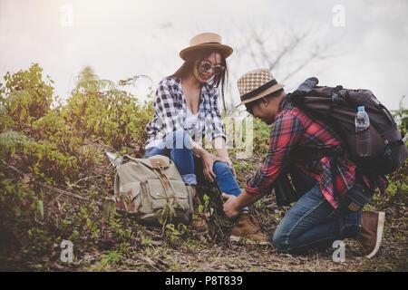 Asian coppia giovane ai viaggiatori di escursionismo caviglia pregiudizio su uno sfondo verde, escursionismo concetto. Foto Stock