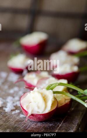 Ravanelli con il burro non salato e sale marino nel buio di sfondo di legno Foto Stock