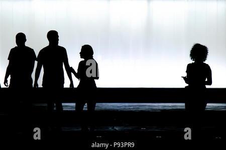 Sfocata sagome di tre giovani amici studenti e un ragazzo è alla ricerca di una nuova ragazza con i capelli ricci in piedi da solo in bianco e nero notte Foto Stock