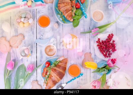 Sfondo con colori diversi. Un family colazione con croissant con rucola e formaggi e caffè aromatico, uova di differenti colori, luminoso piatti e decorazioni di Pasqua, conigli in ceramica. Tulipani freschi