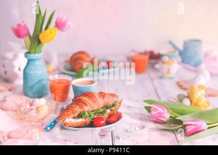 Foto d'epoca. Un family colazione con croissant con foglie di rucola e formaggio e caffè aromatico, uova di differenti colori. Bouquet di tulipani