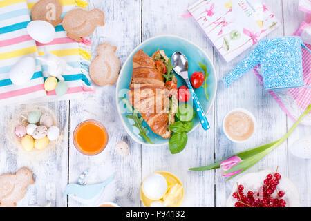 Un family colazione con croissant con rucola e formaggi e caffè aromatico, uova di differenti colori, luminoso piatti e decorazioni di Pasqua, conigli in ceramica. Tulipani freschi di colore rosa.