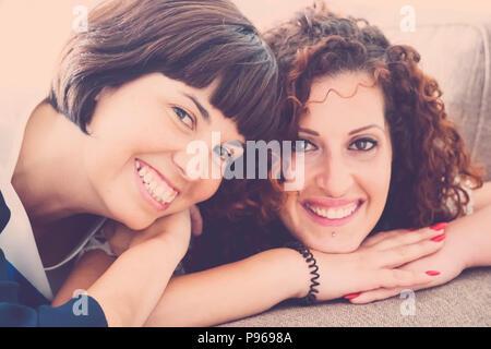 Bel tempo e felicità con ridere e sorrisi per due amici caucasici stabiliscono insieme sul divano di casa. Il concetto di amicizia per immagine interna w Foto Stock