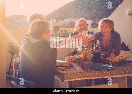 Felice gruppo di adulti celebrare un evento con bicchieri di vino all'aperto in terrazza con il tramonto e la retroilluminazione. dai toni dorati per la felicità lifestyle conc Foto Stock