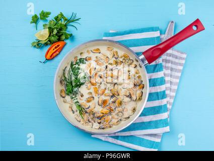 Le cozze in crema di latte y salsa con erbe aromatiche e limone rosso nel recipiente di cottura. Sfondo blu Foto Stock