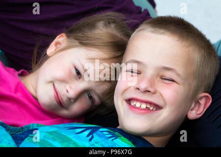 Close-up verticale di due piccoli graziosi bionda felicemente bambini sorridenti, fratello e sorella, un ragazzo e una ragazza che stabilisce nel letto sotto il manto colorato. Incurante in Foto Stock
