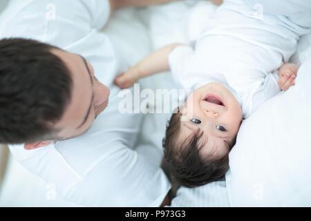 Padre sorridente con il suo Figlio bambino abbracciando a letto Foto Stock