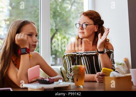 Madre gravi che indossano occhiali aventi in conflitto con la figlia Foto Stock