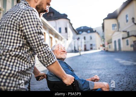 Un adulto figlio col padre senior in sedia a rotelle su una passeggiata in città. Foto Stock