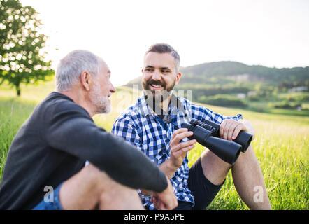 Un adulto hipster figlio con il binocolo e senior padre seduto sul prato soleggiato in natura. Foto Stock