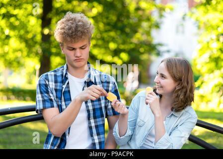 I giovani studenti in estate in un parco all'aperto. Stanno seduti su una panchina in città. Ragazza e sorridenti dà il cibo a guy. Il ragazzo è in imbarazzo. Il concetto di sfiducia. Emozione di gentilezza.