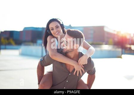 Felici i giovani alla moda giovane divertirsi in città, piggyback di equitazione Foto Stock