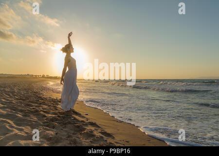 Donna con bracci sollevati, a piedi nudi, sentirsi felice, vivo e libero in natura meditando a Sandy misty respirazione spiaggia fresca e pulita aria dell'oceano al tramonto. Vacanze estive il concetto di stile di vita Foto Stock