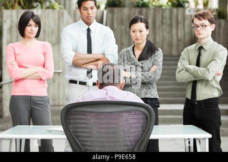 Una razza mista gruppo di gente di affari in piedi di fronte a una persona a una scrivania. Foto Stock