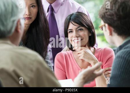 Ispanico busineswoman ascoltando qualcuno parlare durante una riunione di lavoro con altri membri del team. Foto Stock