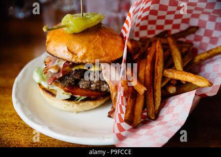 Burger con pancetta e formaggio e peperoncino jalapeno e patatine fritte sul lato. Foto Stock