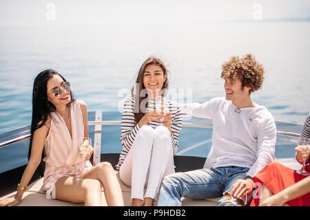Due uomini caucasici invitare tre belle donne per condividere il piacere yacht viaggio sul mare per le isole, i giovani a ridere, e gode di fantastiche vedute del mare Foto Stock