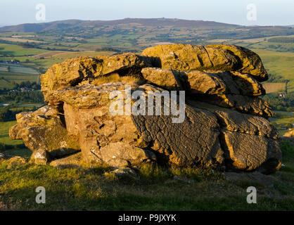 Una formazione rocciosa sulla collina Corndon, Powys, bagnata in serata calda luce del sole, con l'Stiperstones, Shropshire, all'orizzonte. Foto Stock