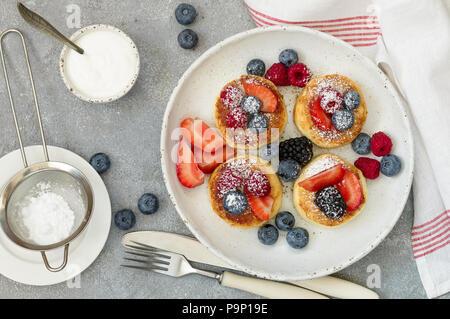 Cottage cheese pancakes, syrniki, frittelle di cagliata con frutti di bosco freschi (lampone, fragola, mirtillo, mora) e zucchero in polvere in una piastra bianca.