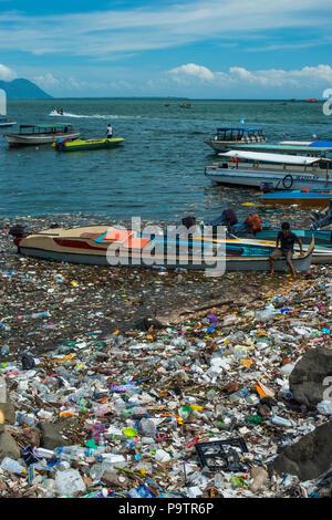 Inquinamento di plastica floating accanto alle piccole imbarcazioni presso il lungomare in Semporna città di Sabah, (Borneo malese, Malaysia. Foto Stock