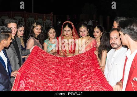 Un matrimonio tradizionale in un piccolo villaggio nella provincia indiana. Indie giugno 2018. Gli sposi portano la sposa allo sposo. Foto Stock