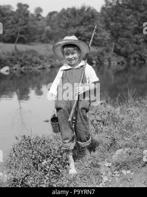 1920s 1930 BAREFOOT BOY STICK porta canna da pesca può di vermi esca indossando cappello di paglia BIB TUTE guardando la telecamera sorridendo - un4795 HAR001 HARS spazio copia a lunghezza completa del flusso di tute da lavoro maschi DENIM ASTA B&W ESTATE contatto visivo libertà felicità allegro avventura ricreazione sorrisi A PIEDI NUDI A PIEDI NUDI Huck Finn gioiosa BIB tuta Tom Sawyer Huckleberry Finn novellame pre-teen pre-teen BOY WORM esca in bianco e nero di etnia caucasica HAR001 in vecchio stile Foto Stock