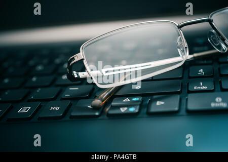 Occhiali giacente sul buio della tastiera del computer Foto Stock
