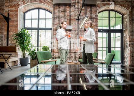 Coppia giovane vestito di bianco in piedi insieme con bevande durante la conversazione nella splendida e spaziosa mansarda interno