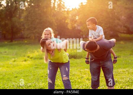 Famiglia, felicità, infanzia e concetto di persone - genitori felici di dare piggyback ride per bambini Foto Stock