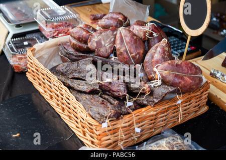 Carne affumicata in una borsa di plastica in un cestello sul negozio Foto Stock