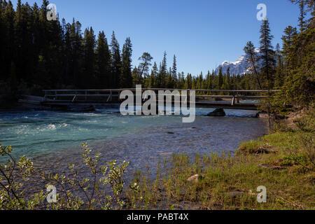 Il fiume che scorre attraverso le Montagne Rocciose Canadesi durante una soleggiata giornata estiva. Prese nel Parco Nazionale di Banff, Alberta, Canada. Foto Stock