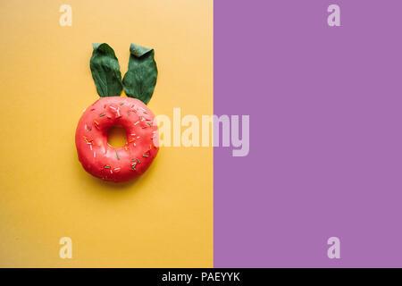 Una ciambella di creativi con le orecchie di foglie che assomigliano a un coniglio su uno sfondo colorato in stile minimale. Nei dintorni di posto per il testo Foto Stock