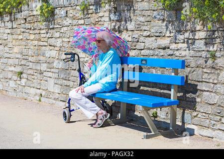 Bournemouth Dorset, Regno Unito. Il 23 luglio 2018. Regno Unito: meteo canicola continua Come temperature aumento su una cocente sole e caldo giorno a Bournemouth spiagge con un cielo azzurro e sole ininterrotta. Sunseekers in testa al mare a prendere il sole. Senior donna seduta da sola sulla passeggiata sotto un ombrello che offre una certa protezione dal calore. Credito: Carolyn Jenkins/Alamy Live News Foto Stock
