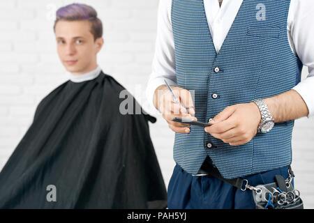 Foto ritagliata del barbiere mantenendo in plastica nera Pettine e forbici istanding davanti ofyoung client. Ragazzo avente tonica in viola colore dei capelli e guardando la fotocamera. Master indossando le forbici caso, corpetto. Foto Stock