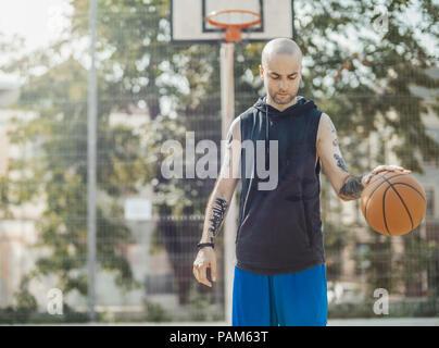 Bald attraente uomo giocare a basket sul campo da basket. L uomo è messa a fuoco e il colore di primo piano e sfondo sfocato. Foto Stock