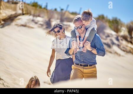 La famiglia felice di camminare sulla spiaggia insieme Foto Stock