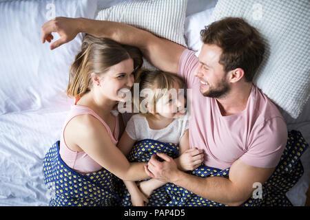 La famiglia felice giacente in letto, coccole Foto Stock