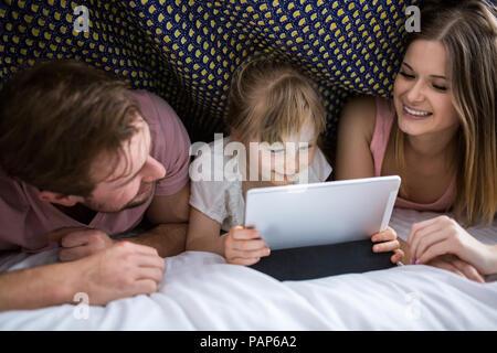 I genitori guardare qualcosa sulla tavoletta digitale con la loro figlia sotto coperta a letto Foto Stock