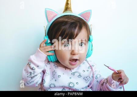 Ritratto di sorpreso bambina con cuffie unicorn Foto Stock