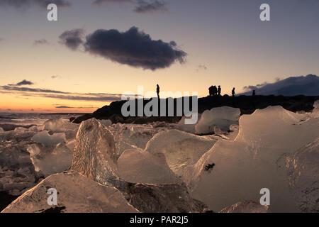 Un turista sta stagliano contro il cielo della sera come guardare il tramonto sulla spiaggia di diamante nel sud dell'Islanda Foto Stock