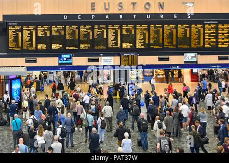 Vista da sopra guardando giù all interno della stazione dei treni di Euston concourse con passeggeri visualizzazione treno partenze Informazioni di viaggio Londra REGNO UNITO