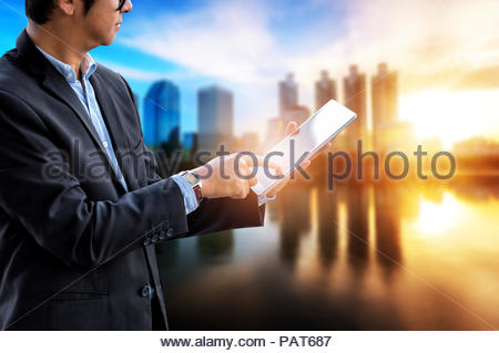 La Strategia aziendale Progetto di avvio concetto, imprenditore tablet touch a portata di mano e la città di sfocatura dello sfondo crepuscolo, le tendenze del business in alta risoluzione Foto Stock