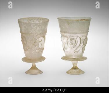 Coppe con decorazione applicata. Data: 11th-inizi del XII secolo. Questi matcing calici sono formate ciascuna da una coppa conica attaccato ad un piccolo, solido e strombate piede derivava da una flangia circolare applicata intorno alla base del bicchiere. Essi sono fatti di colore giallastro vetro incolore che contiene molte piccole bolle. Entrambe le coppe sono decorate con una ininterrotta sentiero applicata nello stesso colore giallognolo, che forma una linea orizzontale di circa due terzi dell'altezza e continua qui sotto per creare un fantasioso, configurazione astratta di parentesi progetta attorno al bicchiere. La decorazione può essere letto più chiaramente quando la coppa è