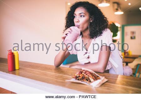 Giovane donna bere il frullato al chiuso Foto Stock