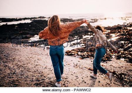 Vista posteriore di due ragazze in piedi sulla spiaggia contro il cielo chiaro Foto Stock