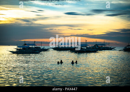 Silhouette di quattro turisti nuotare e giocare in mare nei pressi di barche da pesca al tramonto - Isola di Malapascua, Cebu - Filippine Foto Stock