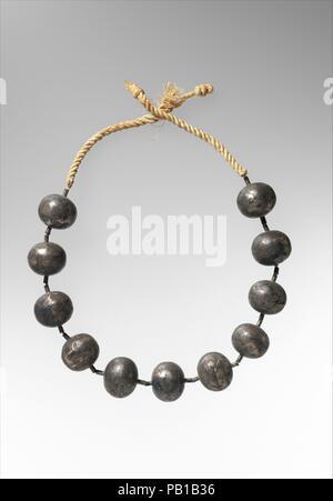 Collana di Wah. Dimensioni: L. della collana 70,5 cm (27 3/4 in.); Massima diam. 3.2 cm (1 1/4 poll.); più piccola diam. 2,5 cm (1 in.). Dynasty: Dynasty 12. Regno: regno di Amenemhat i primi. Data: ca. 1981-1975 A.C. Dopo il wah della mummia era stata parzialmente avvolto, questa collana di perle di argento è stato legato attorno al collo. Le perle sono state infilate su dodici o più trefoli di filo che sono state poi ritorti attraverso legami di spessore corda di lino. Tre altre collane era stato posto sulla mummia nella stessa posizione. Uno di questi è costituito da sfere d'oro (40.3.17); uno è fatta di maioliche blu perline (40.3.18); Foto Stock